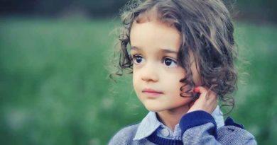 Девочка с кудряшками на фоне зеленого поля